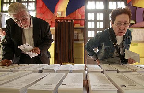 Dos españoles contemplan las papeletas en el colegio Pi i Margall en Madrid. | Antonio Heredia
