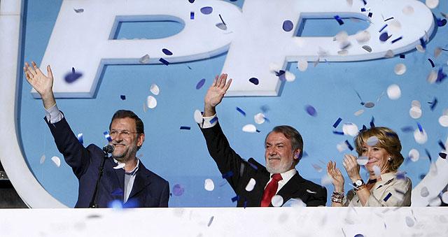 Mariano Rajoy saluda desde el balcón de Génova, junto a Jaime Mayor Oreja y Esperanza Aguirre. | Efe
