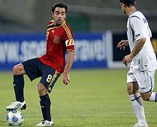 Xavi pisa el balón ante un rival. | Efe