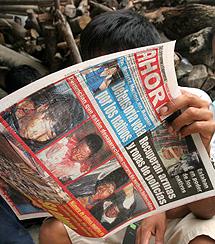 Dos indígenas leen las informaciones sobre los disturbios en Bagua.   Efe