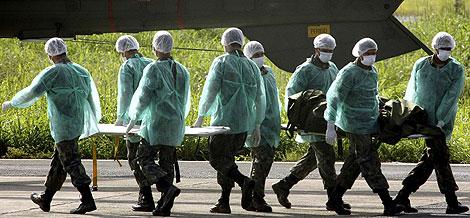 Miembros de la Fuerza Aérea brasileña trasladan el cuerpo de una víctima. | Reuters