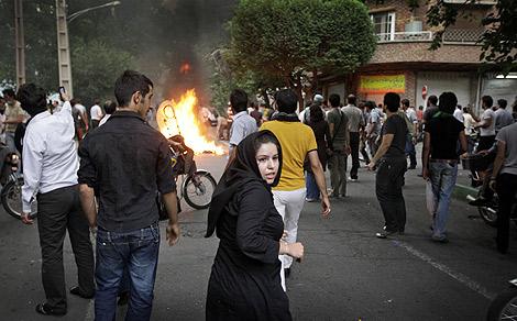 Una mujer con atuendo tradicional vuelve la vista atrás durante las protestas de los partidarios de Musavi en las calles de Teherán. | Ben Curtis (AP)
