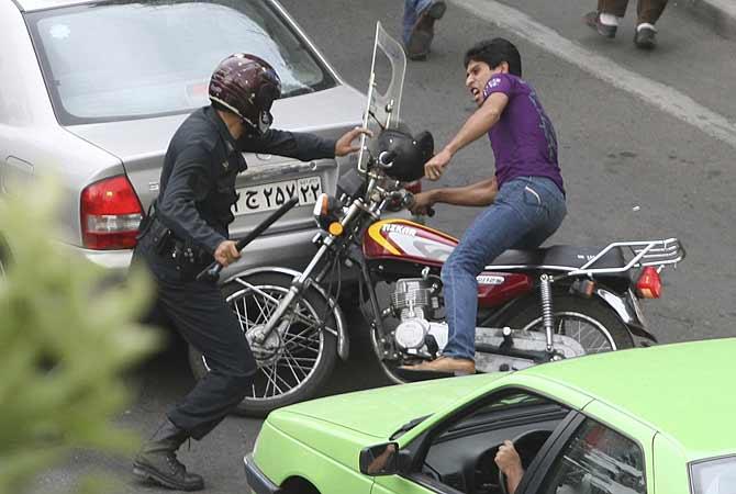 Un policía golpea a un motociclista durante una protesta en Teherán.   Reuters