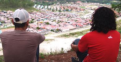 Dos jóvenes en un cerro mirando a Ciudad España. | I.Molero