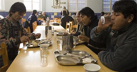 Varias personas almuerzan en un comedor de Cáritas. | El Mundo