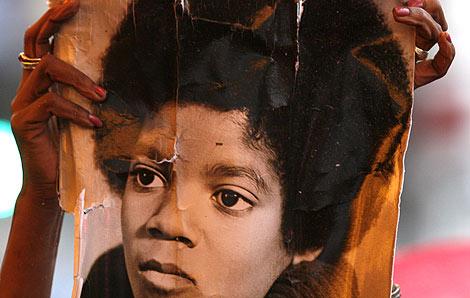 Un fan sujeta una foto de Michael Jackson, en el homenaje en el Teatro Apolo. | Reuters