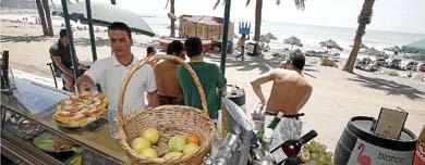 Un camarero recoge una bandeja en una playa de la Costa del Sol. | elmundo.es