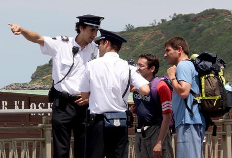 Dos efectivos de la Guardia Municipal asesoran a unos turistas. | Andrea Anguita
