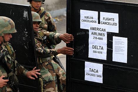 Unos carteles informan del cierre del aeropuerto de Toncontín.   AFP