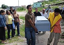 Familiares de una de las víctimas portando el féretro.   AFP
