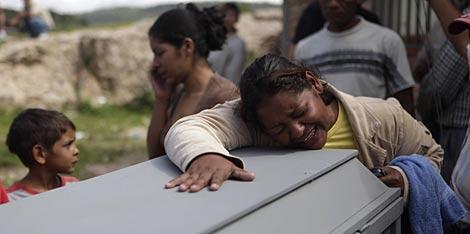 Rebeca Murillo llora sobre el ataud de su hermano, Isy Murillo, uno de los fallecidos. | AP