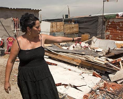 Una mujer señala un cobertizo adyacente a su casa destrozado por la piqueta municipal. (Xouvanoba)