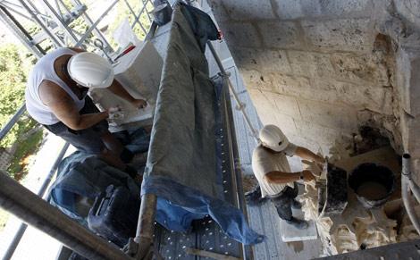 Dos operarios trabajan en las labores de restauración. | Pablo Requejo