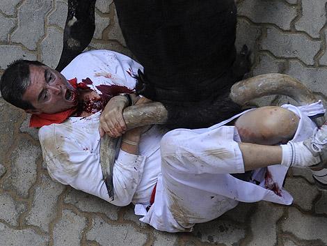 El toro 'Ermitaño' ha corneado a un mozo en el callejón en el sexto encierro. | Iban Aguinaga | Efe