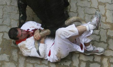 El toro 'Ermitaño' embiste a un mozo, durante el encierro del domingo. | Efe