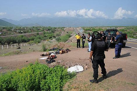 La Policía inspecciona los cuerpos de varias personas asesinadas a los pies de una autopista en Michoacán. | Efe