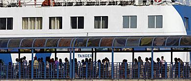 Pasajeros aguardan cola para embarcar rumbo a África.   Efe