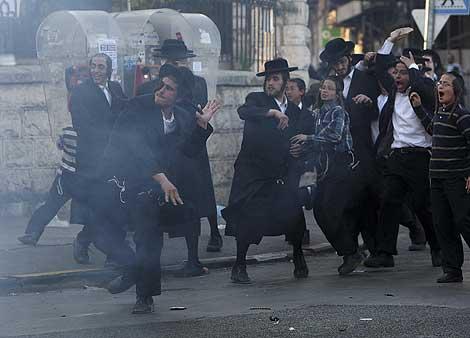 Ultra-ortodoxos judíos lanzan piedras contra la policía por la detención de la mujer.   Reuters