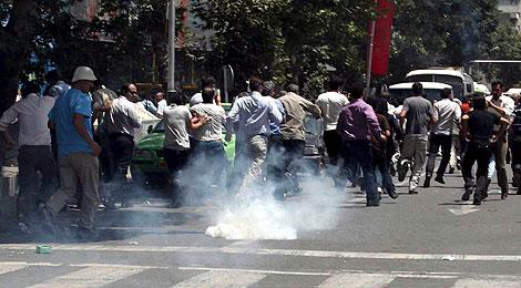 Un grupo de manifestantes se protege de los gases lacrimógenos de la policía. | Efe