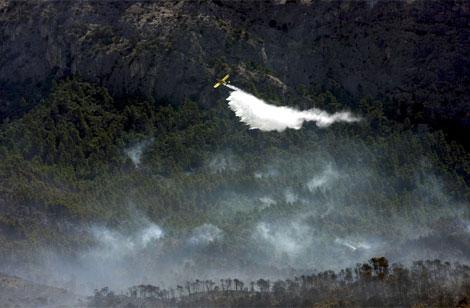 Uno de los aviones de los bomberos trabajando en la extinción. | Efe