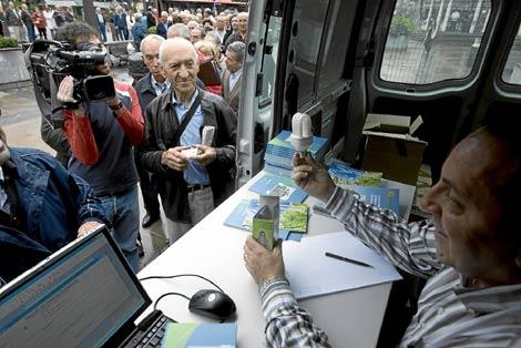 Una multitud de ciudadanos hace cola para recibir su bombilla de bajo consumo. | Carlos García