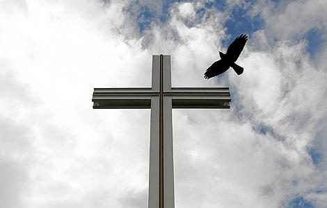 Un cuervo vuela sobre la cruz papal del Parque Phoenix, cerca de Dublín. | Reuters