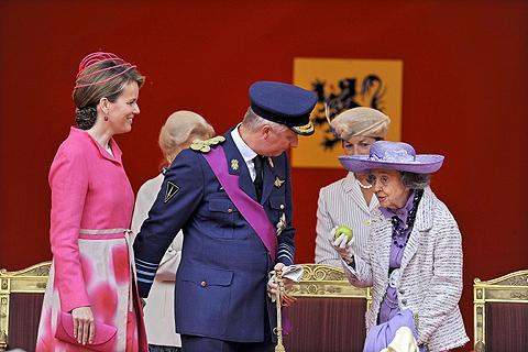 La reina Fabiola de Bélgica muestra la manzana mientras observa el desfile del Día Nacional de Bélgica junto al principe Felipe y su esposa Matilde. | Efe