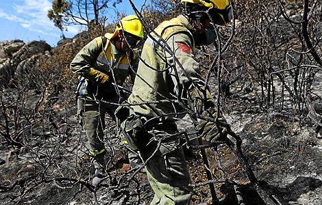 Dos miembros de un retén forestal, trabajando en la zona quemada de Collado Mediano (A. M. X)