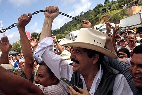 Zelaya (con sombrero) levanta la cadena que separa la frontera.   AFP