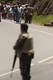Partidarios de Zelaya se alejan de los soldados que detuvieron su bus.   AP