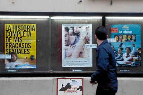 Un joven observa la cartelera de un cine. | Jesús Domínguez