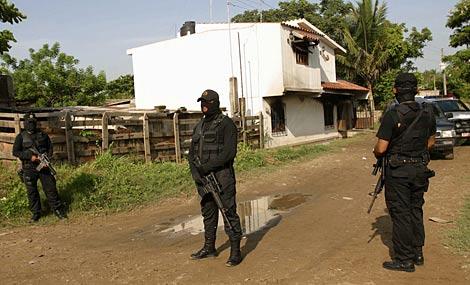 Varios agentes escoltan la casa del policía asesinado junto a su familia.   Efe
