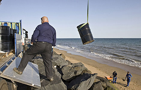 Operarios de Cepsa descargan bidones en la playa de Huelva para recoger el crudo. | Efe