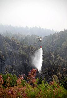 Un helicóptero suelta una carga de agua. | Efe