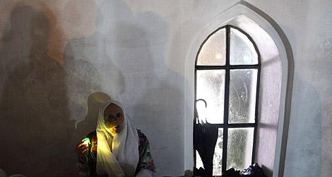 Una mujer bosnia reza en la aldea de Prusac.   Reuters