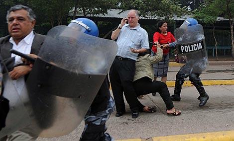 La rectora, con chaqueta clara, cae al suelo ante un agente.   AFP