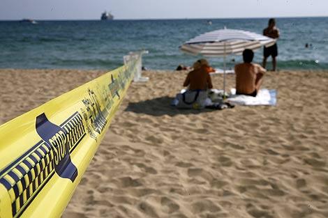 Varias personas disfrutando de la playa en el límite del cordón policial. | Ap