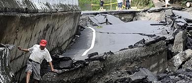 Un hombre intenta caminar entre una carretera destrozada.   Reuters