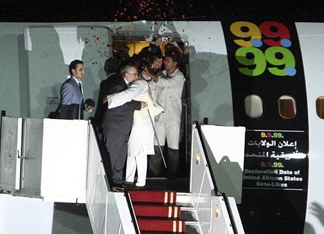 El excarcelado es abrazado por el hijo del líder libio Gadafi en Tripoli | AP