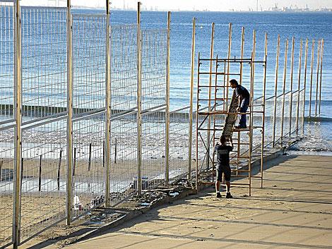 Operarios colocando las vallas de separación en plena playa.   J. F. Ferrer