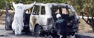 Efectivos de la Guardia Civil inspeccionan el coche carbonizado.   Benito Pajares