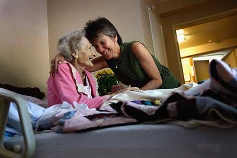 Una enfermera del plan de salud 'Medicare' abraza a una paciente de 83 años sin recursos.   AFP