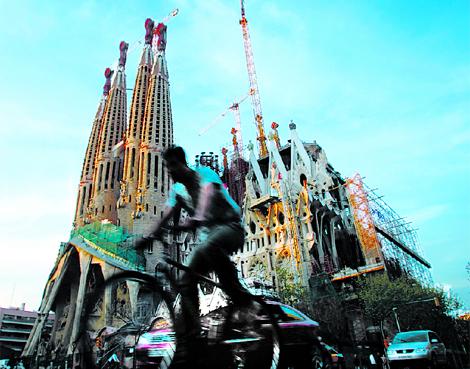 Un barcelonés pasea en bicicleta ante la Sagrada Familia. | Antonio Moreno