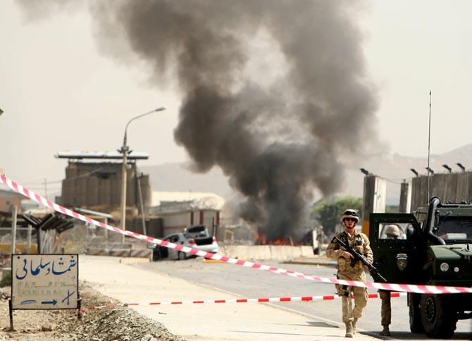 Soldados de la ISAF patrullan en el lugar donde se registró la explosión de un coche bomba, junto al aeropuerto militar de Kabul.| STR