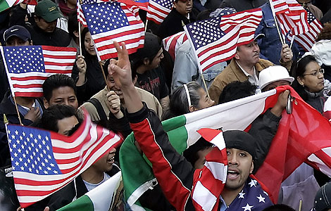 Latinos agitan banderas de EEUU y México durante una manifestación.   AP