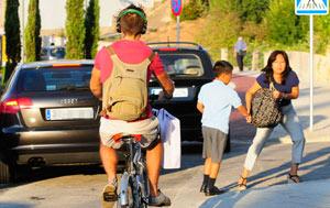 Una madre lleva a su hijo al colegio en presencia de un ciclista. | Cati Cladera