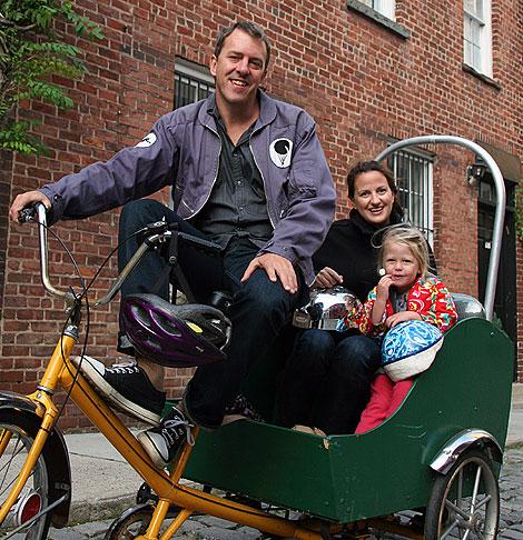 Colin Beavan, junto a su mujer e hija, a bordo de su triciclo. | Paul Dunn/Yes Magazine