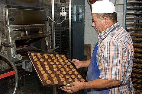 Un maestro artesano con una bandeja de mantecados listos para hornear. | Quino Castro