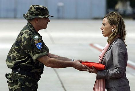 El coronel García Blázquez entrega a Chacón la bandera que ondeó en Kosovo. | Reuters
