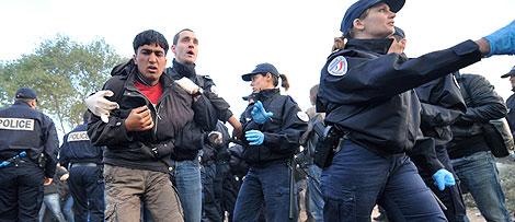 Varios agentes trasladan a uno de los inmigrantes arrestados. | AP